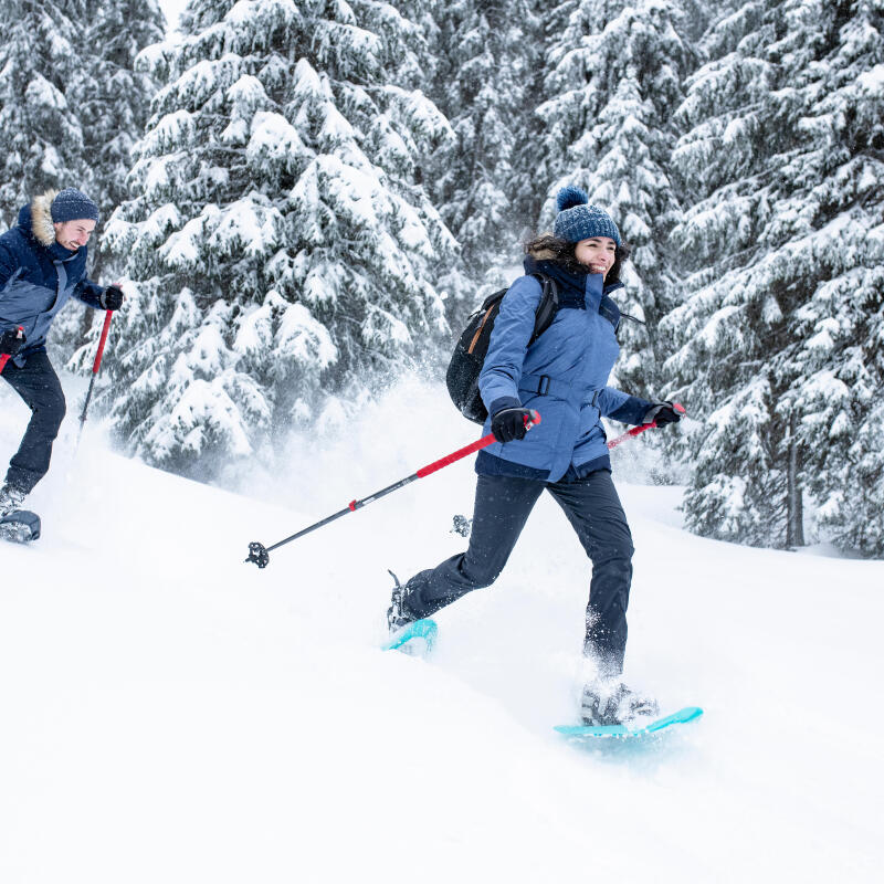 man and woman snowshoeing in the forest