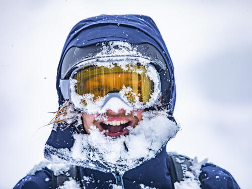A man with a face full of snow protected by ski goggles
