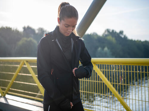 Woman running on a bridge with multilayered clothing