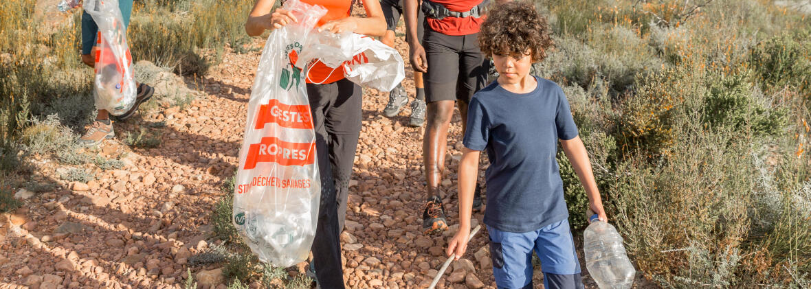 A family on a nature hike picks up trash