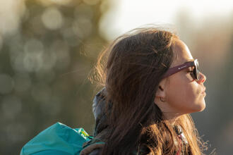 Jeune femme, les yeux fermés, profitant du soleil