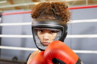 Boxeuse avec ses gants rouge et  son protecteur facial