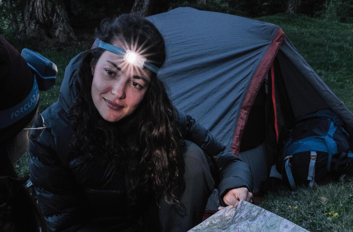 femme en camping avec une lampe frontale