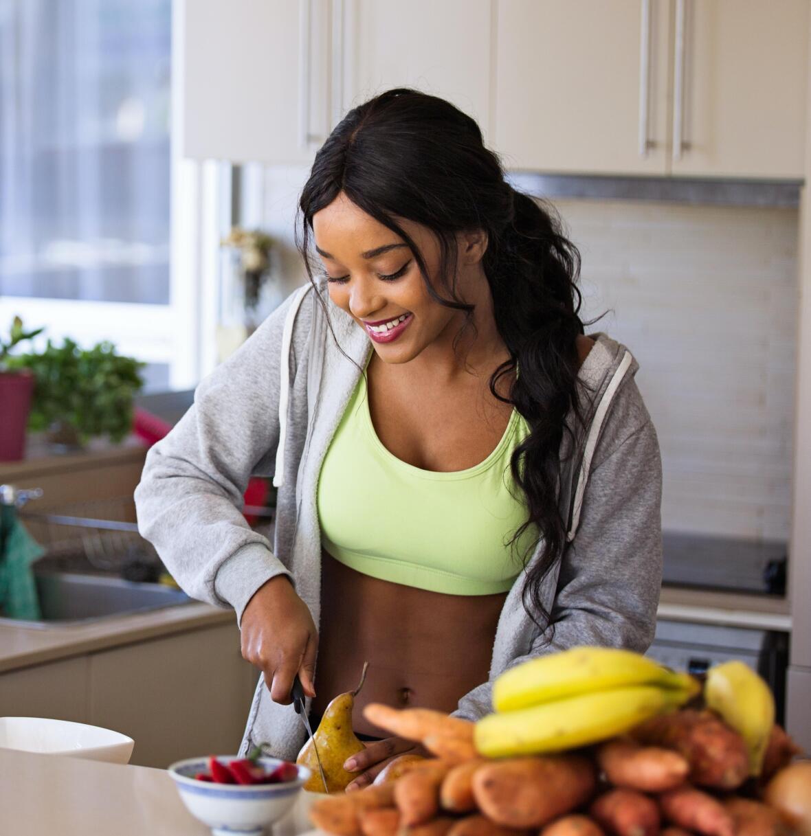 Une femme coupe des fruits dans une cuisine