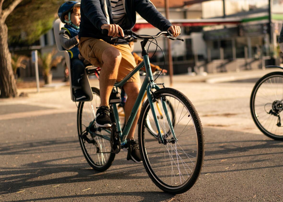 un papa sur son vélo hybride avec son enfant à l'arrière