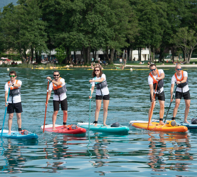 group of people practicing stand up paddle