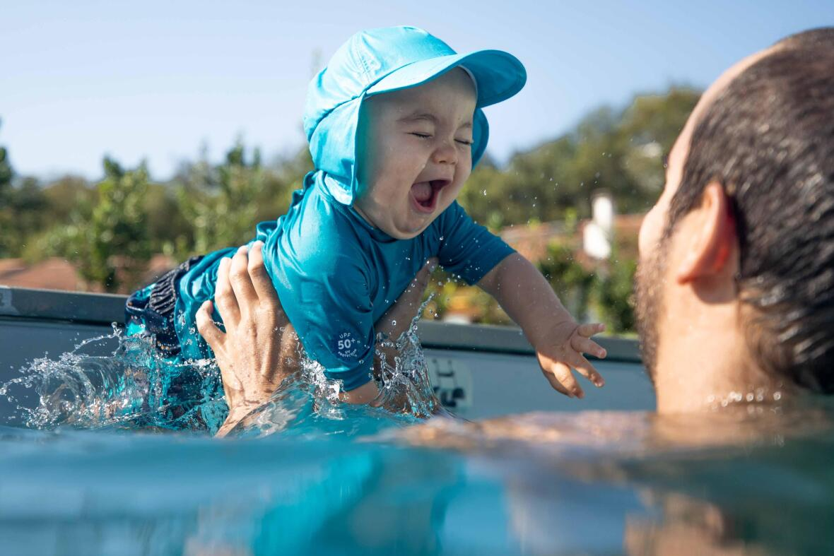 a kid jumps in water on daddy's arms