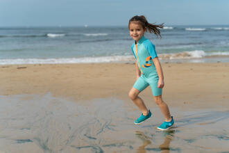 Petite fille qui s'amuse sur la plage