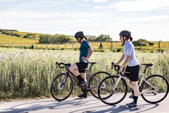 women cycling along fields