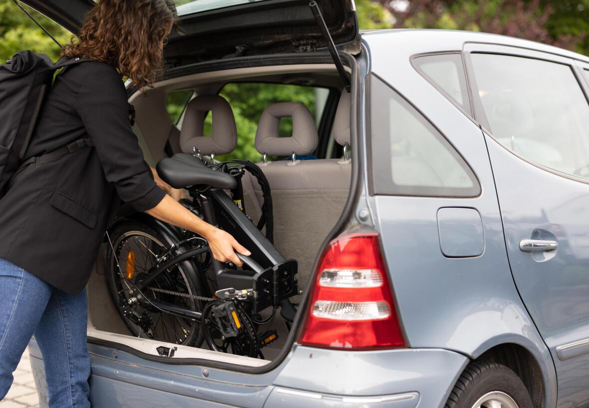 femme qui place son vélo pliant dans son coffre de voiture