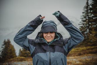 woman smiling in the rain wearing a rain jacket