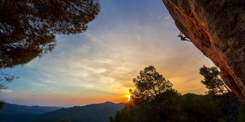 coucher de soleil avec un grimpeur sur une paroi rocheuse