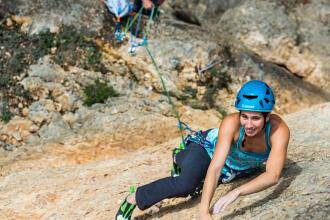 Une femme escalade une paroi rocheuse