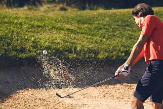 un homme frappe la balle hors d'une fosse de sable