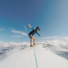 enfant debout sur sa planche de surf avec un casque