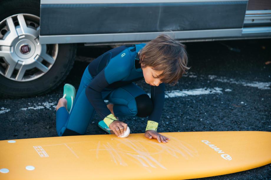 enfant qui waxe sa planche de surf en mousse decathlon