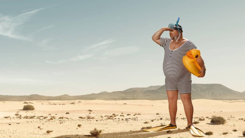 Im Bildmittelpunkt steht ein korpulenter Mann in schwarz-weiß gestreiften Retro-Badeanzug. Er trägt Schwimmflossen an den Füßen, Badekappe und Taucherbrille mit Schnorchel auf dem Kopf und einen kleinen gelben Schwimmreifen in Form einer Ente unter seinem Arm. Er blickt suchend nach links in die Ferne und hält dabei eine Hand mit der Handkante auf Höhe der Augenbrauen, um seine Augen vor der Sonne abzuschirmen. Er hält Ausschau nach Wasser, jedoch steht er mitten in einer Wüstenlandschaft.